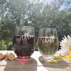 Netflix and Chill Funny stemless wine glasses with red wine and white wine on wood table top with 2 wine corks and flowers in city park.