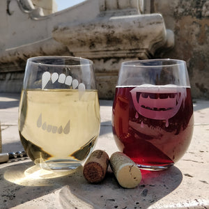 Stemless wine glasses pair of 2 with etched with Werewolf and Vampire teeth filled with white wine and red wine in a Gothic bridge background with a wine cork and wine opener