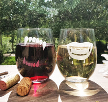 Stemless wine glasses pair of 2 with etched with Werewolf and Vampire teeth filled with white wine and red wine in park on wood table top with two wine corks and wine opener with trees in background