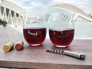 Stemless wine glasses pair of 2 with etched with Werewolf and Vampire teeth filled with white wine and red wine placed on a wood plank with cork and wine bottle opener near futuristic back drop in Valencia Spain