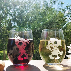Fun Zombie male and zombie female stemless wine glass set etched with red wine and white wine on wood table top in park wine cork and sun setting on trees.