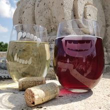 Stemless wine glasses pair of 2 with etched with Werewolf and Vampire teeth filled with white wine and red wine near a stone cobble with two wine bottle corks