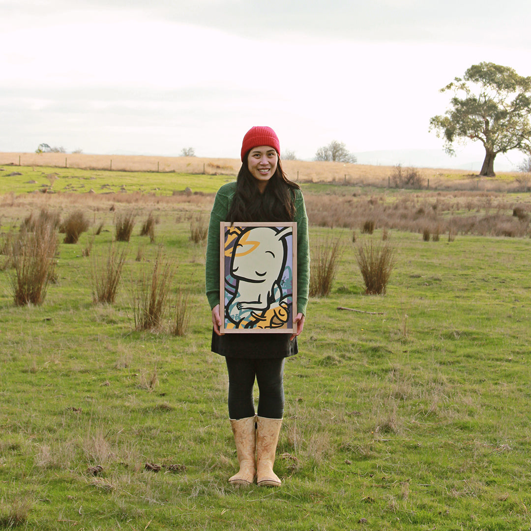 noferin holding paintings australian landscape red beanie artist