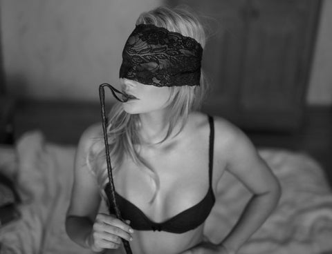 Blindfolded lady holding a whip showing a BDSM session about to start