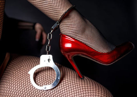 Lady wearing red heels with cuffs around her ankles