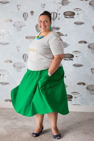 Eli in a plus-size green cotton a-line skirt with pockets