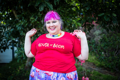 A fat babe in an organic cotton red t-shirt that says HOUSE OF BOOM across it