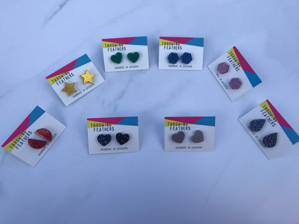 eight pairs of glittery stud earrings in various shapes and colours