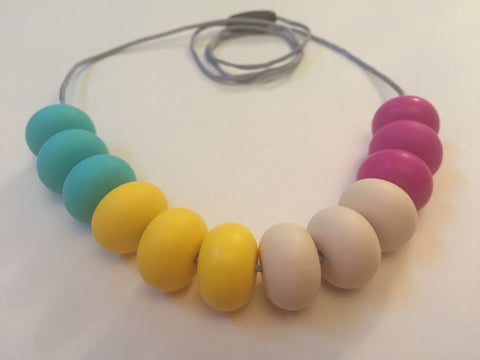Turquoise, yellow, ecru and magenta donut-shaped silicone bead necklace