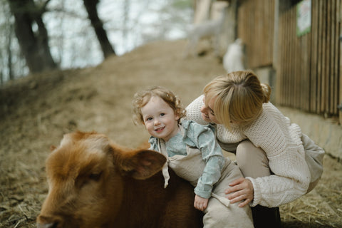 mother holding her young child on a cow