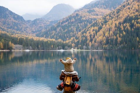 A backview of a hiker with a small child on their shoulders viewing a beautiful mountain lake scene