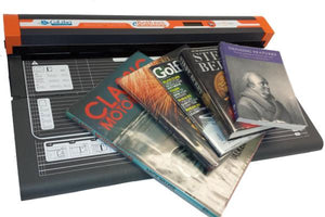 An image of the CoLibri Systems clear book covering machine for large books and quantities of books. There are a few books and a magazine on top of the machine.