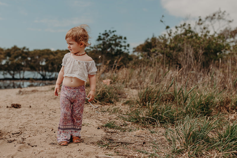 Kids Bohemian style bell bottoms in a pink bohemian border print, exclusive to We the Wild Collective