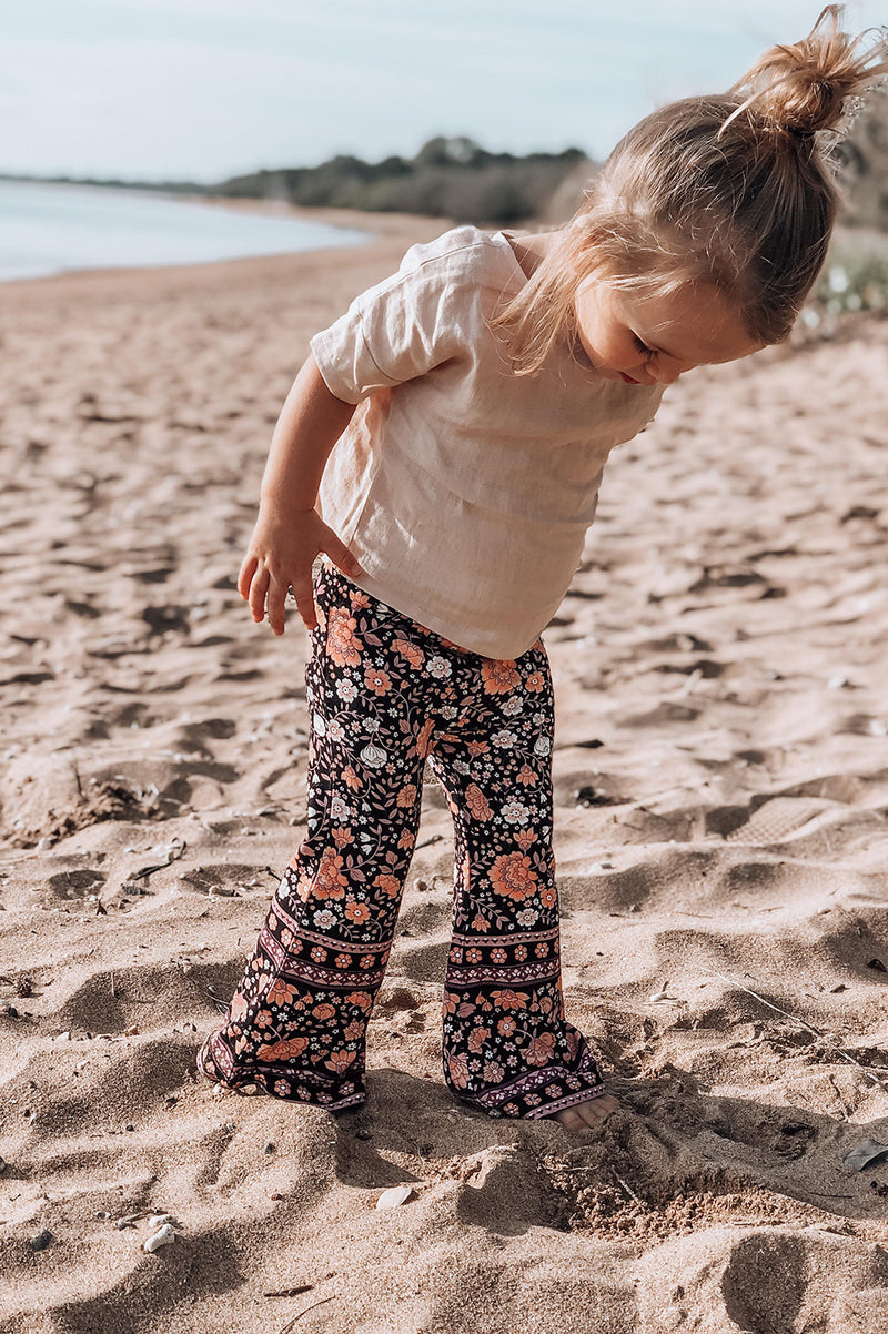 Melbourne Mini Bell bottoms in a black based floral border print. Bohemian inspired kids fashion, exclusive to We the Wild Collective