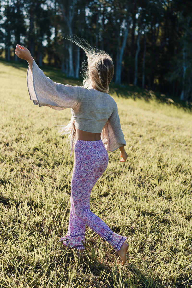 Women's Bohemian style bell bottoms in a pink bohemian border print, exclusive to We the Wild Collective