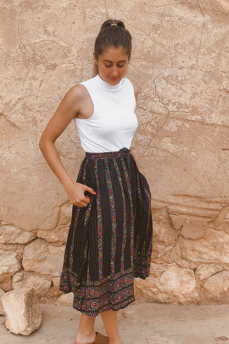 Summer Daze midi length skirt in Paisley black based border print. Elastic waistline, side pockets and self fabric waist tie with beaded tassel ends. exclusive to We the Wild Collective