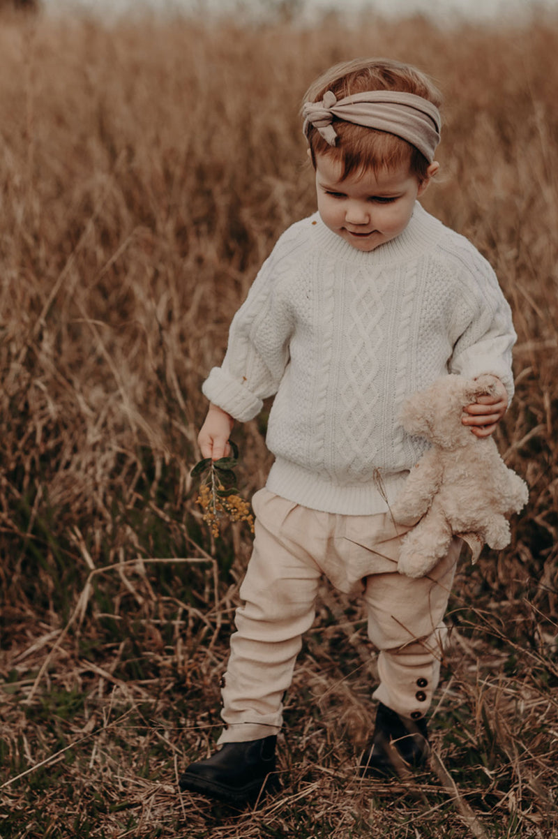 Kids, Bohemian style pant made from pink, 100% linen. Merino Wool cable knit sweater in colour Milk. Exclusive to We the Wild Collective