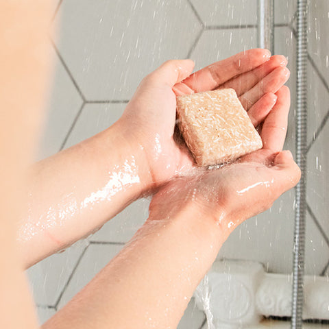 Hands holding solid shampoo bar in shower