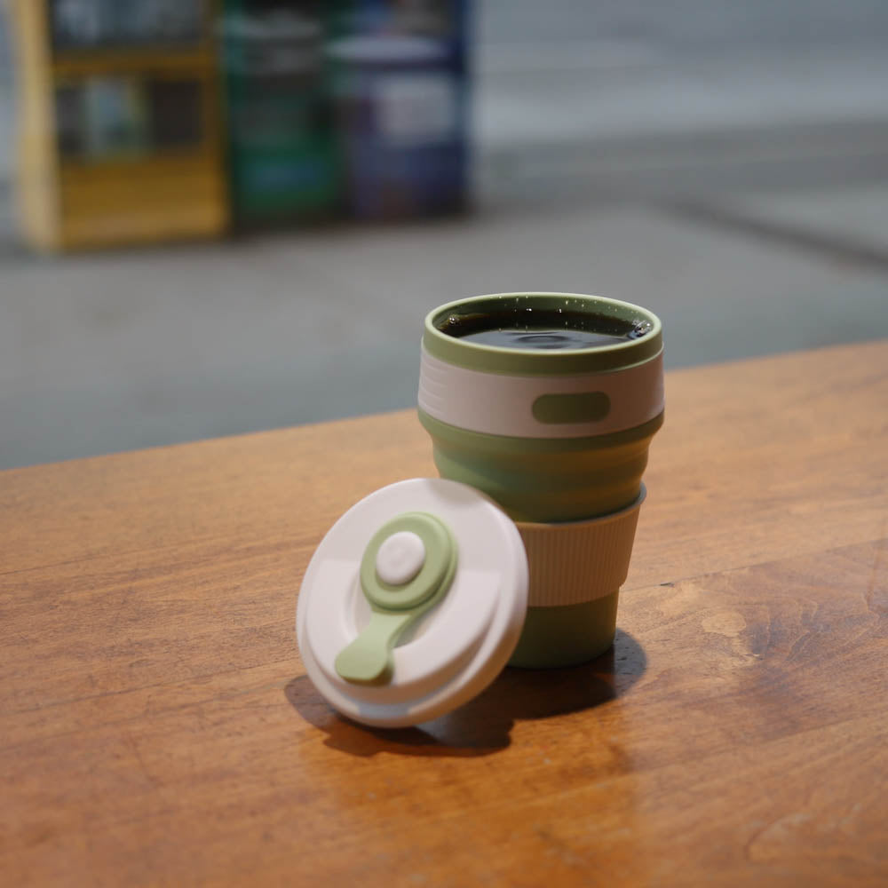 collapsible coffee cup lifestyle - green coffee shop