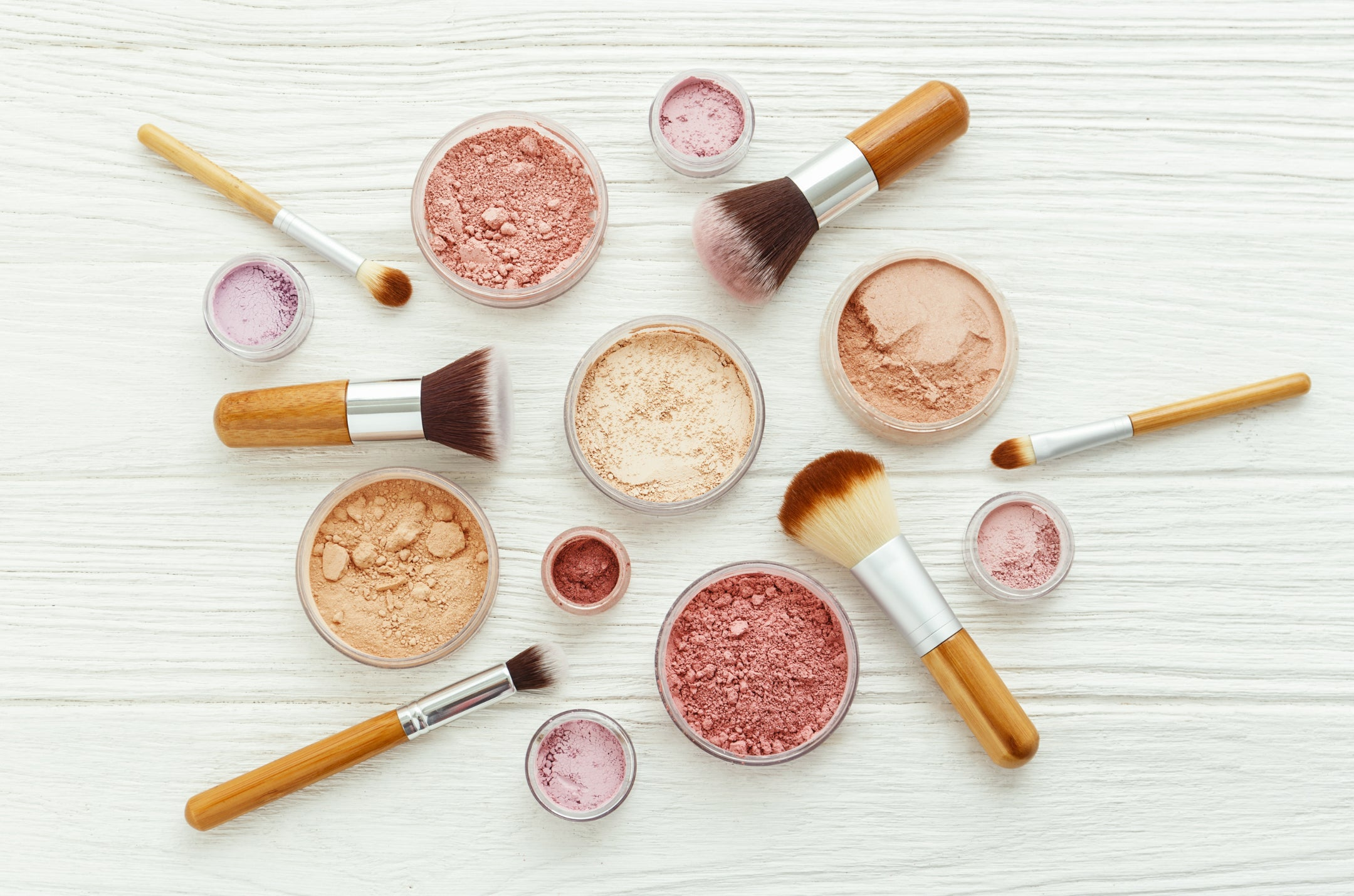 Powdered makeup along with makeup brushes placed on a white wooden surface