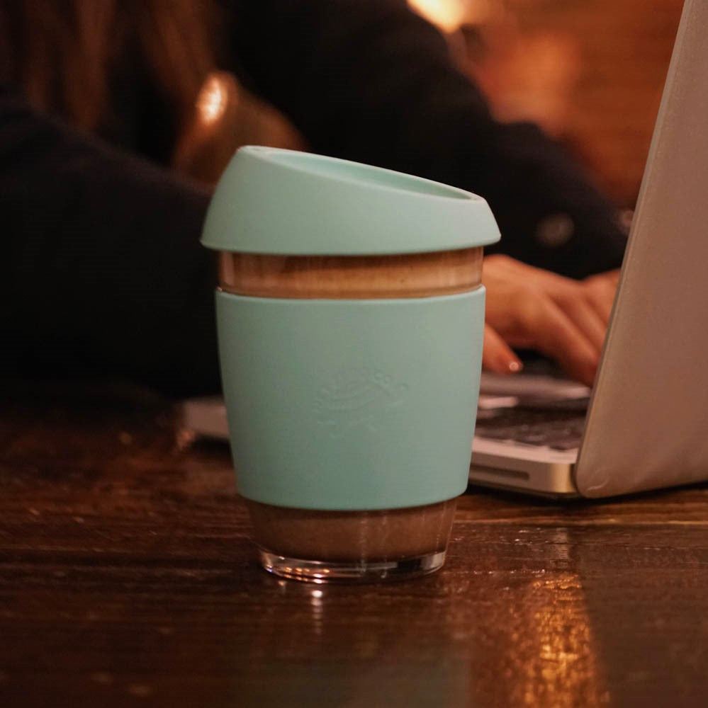 silicone glass coffee cup lifestyle - blue with computer