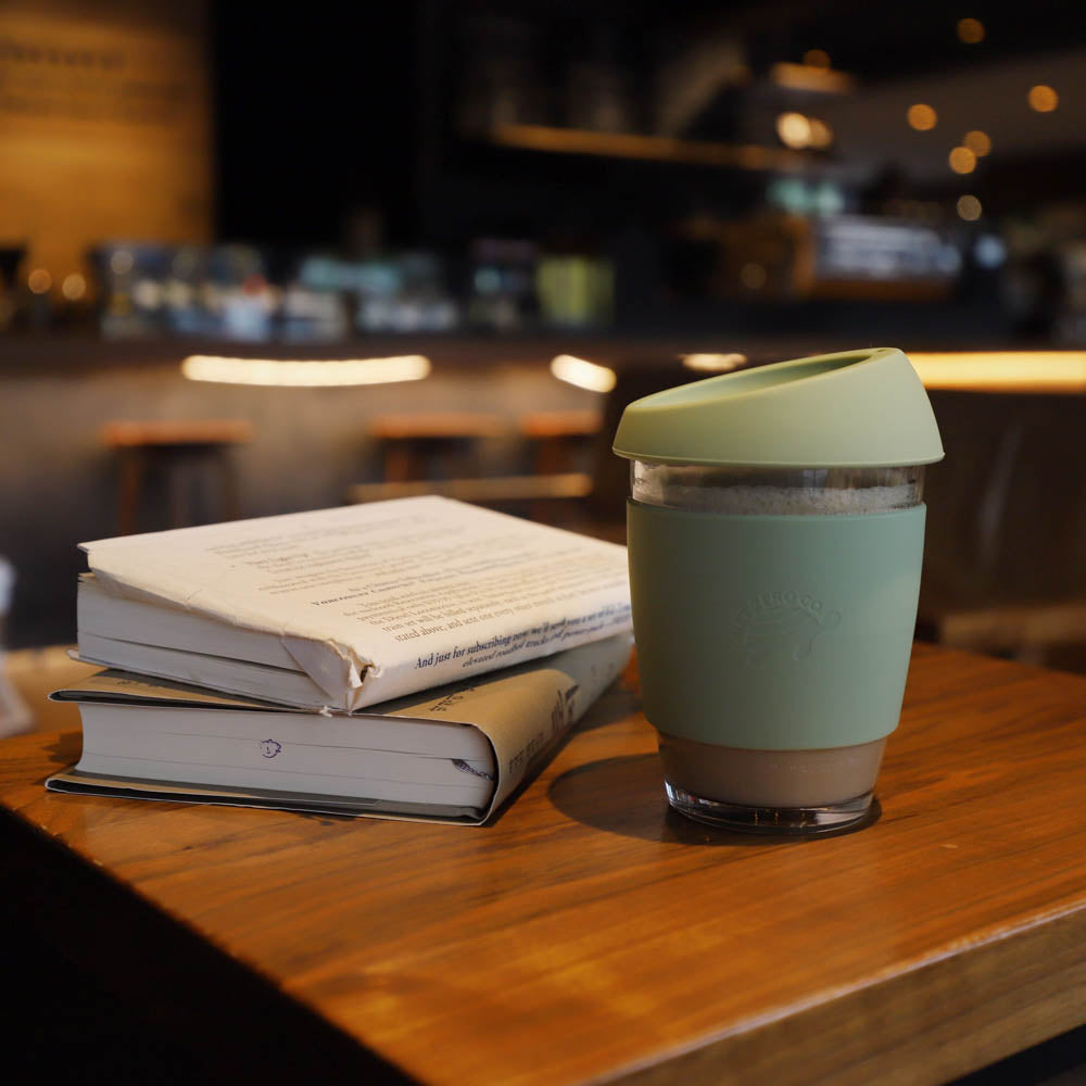 silicone glass coffee cup lifestyle - green with books