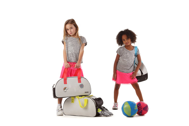 Kids holding their Duffy Kids Ultra Light Travel Bag With Shoe Compartment Pink.jpg