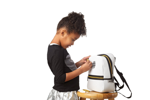 girl adding the DIY nimicks on a Stark Kids Light Backpack Gold Edition.jpg