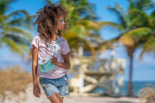 Girl by the beach wearing the Convertible Kids Fanny Pack in Green