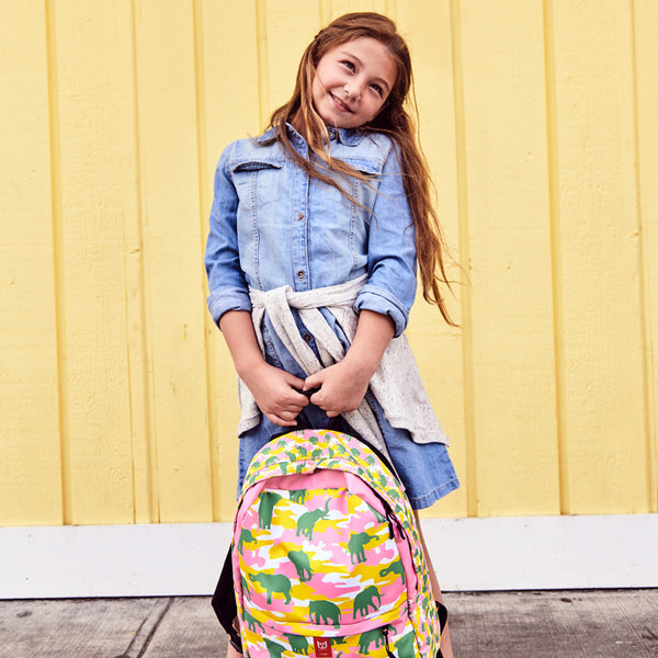 Girl model holding Camo Backpack | Elephants | In Pink, Yellow, and Green. Front view.