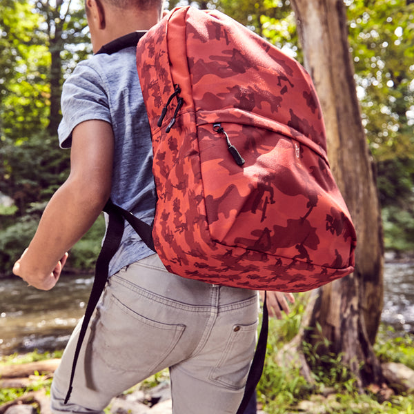 Male model wears Camo Backpack | Skateboard | In Reds. 3/4 view.
