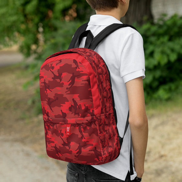Male model wears Camo Backpack | Soccer | In Reds. 3/4 view.