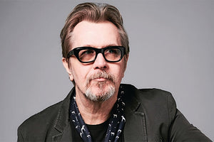 Gary Oldman wearing tinted thick-framed glasses