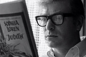 Michael Caine wearing glasses reading newspaper