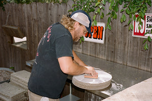 Kevin Hockin stamping his Side Pie pizza boxesSide Pie pizza box and Garrett Leight California Optical Wilson sunglassesKevin Hockin making Side Pie pizza at his home in Altadena