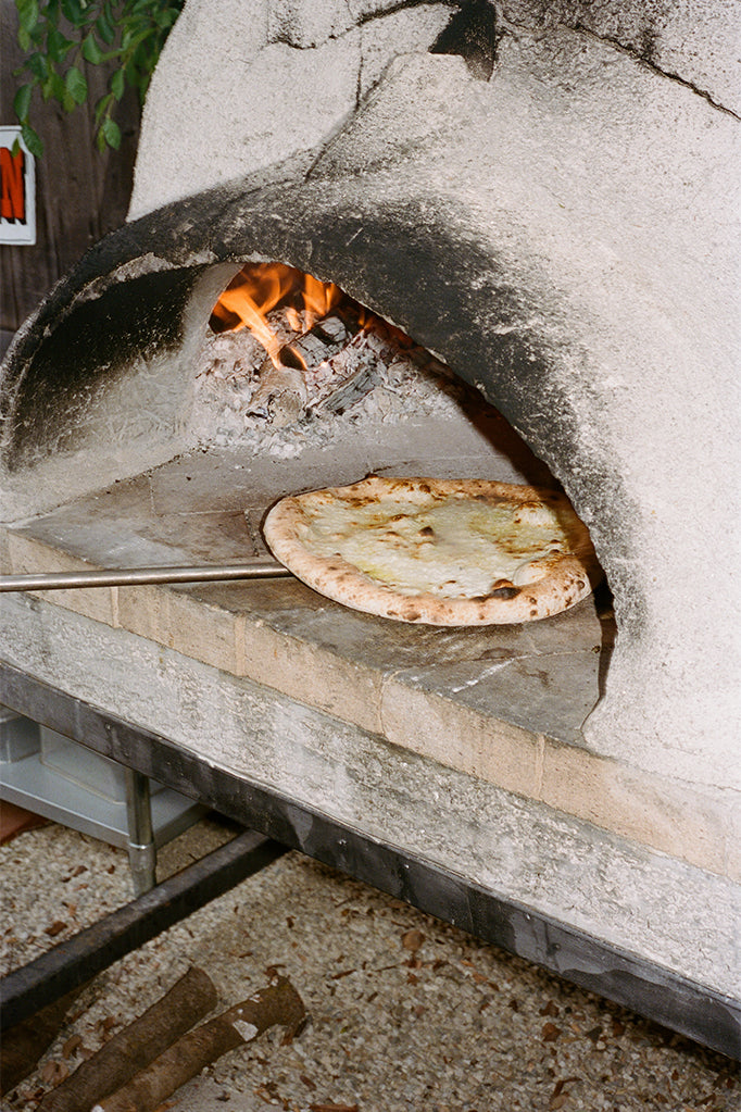 Side Pie pizza going in stone oven