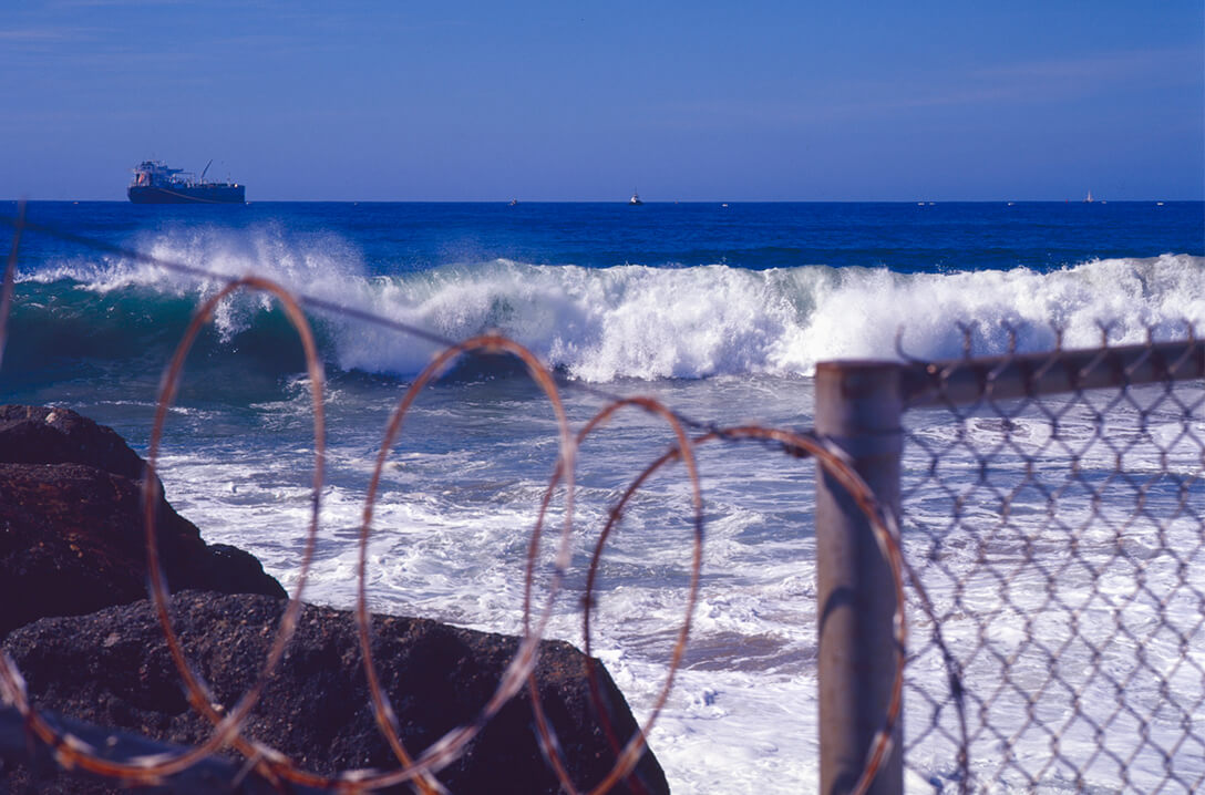 wave crashing in front of barred gate