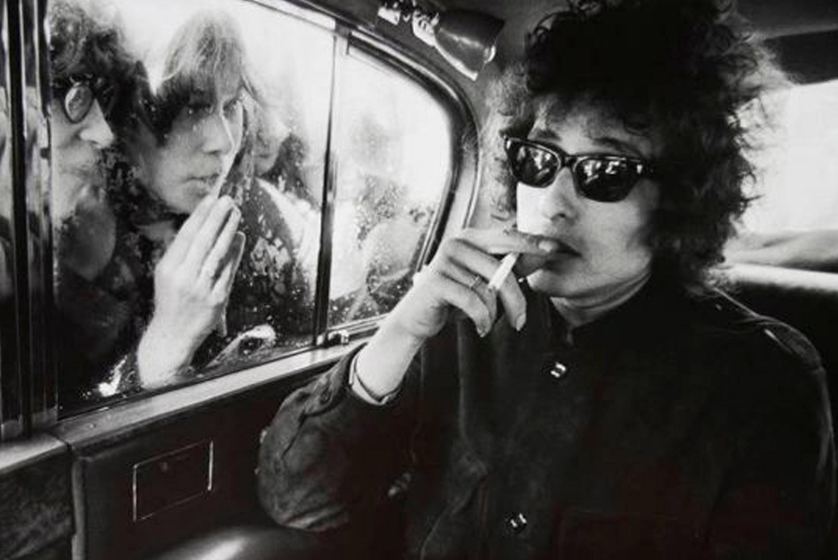 black and white photo of Bob Dylan wearing sunglasses