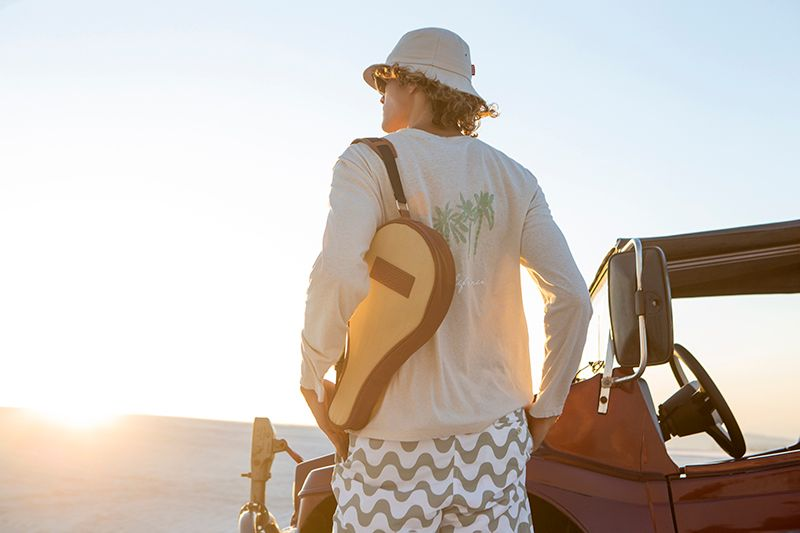 Man wearing Frescobol Carioca Ace sunglasses, bucket hat, long sleeve graphic tee, and graphic shorts