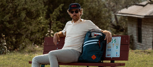 Erik Anders Lang wears GLCO x Jones Kinney Sunglasses and backpack