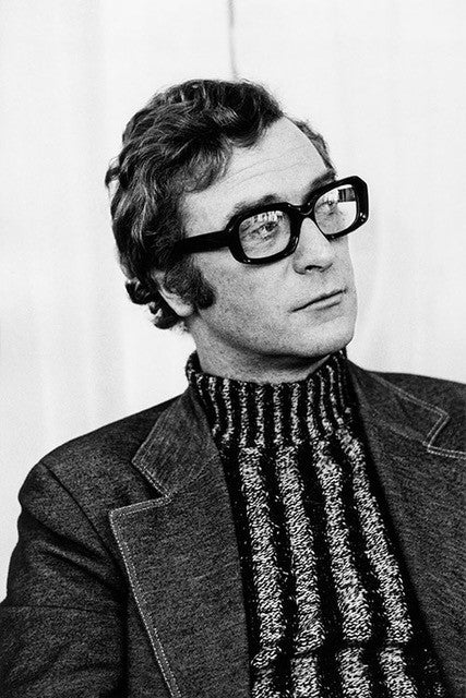 Black and white photo of Michael Caine wearing glasses