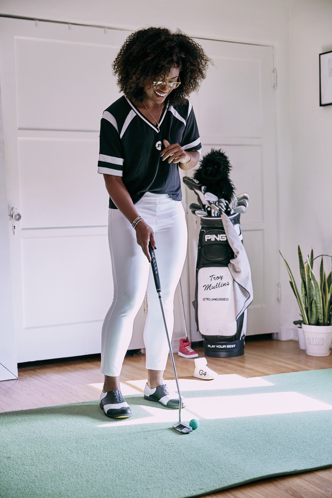 Troy Mullins at home holding a golf club
