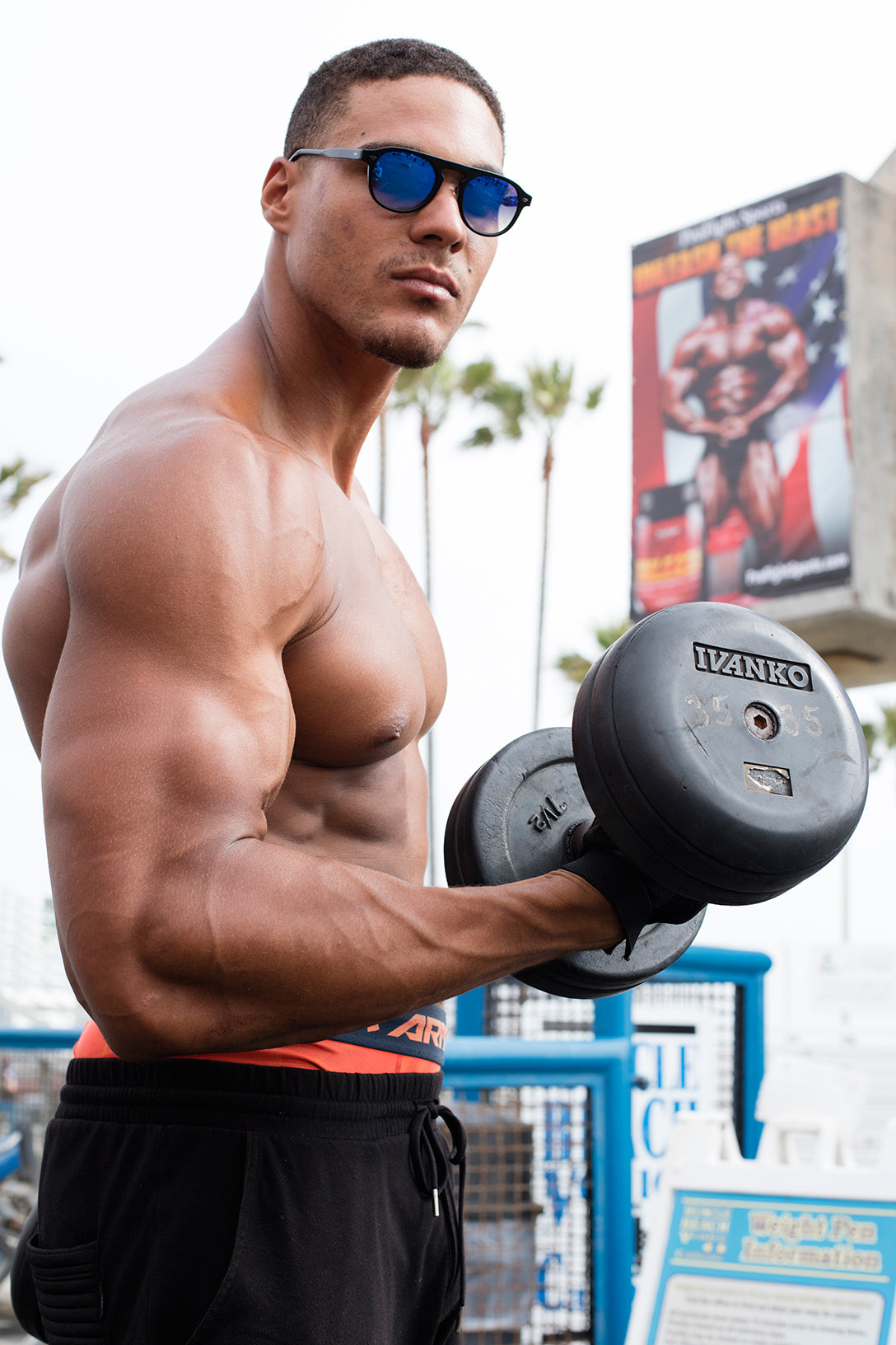 Muscle beach body builder poses with a 35lb dumbbell GLCO sunglasses
