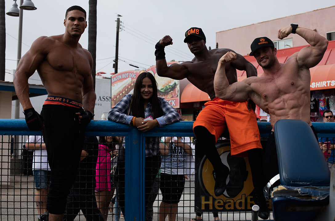Muscle beach body builders pose with person