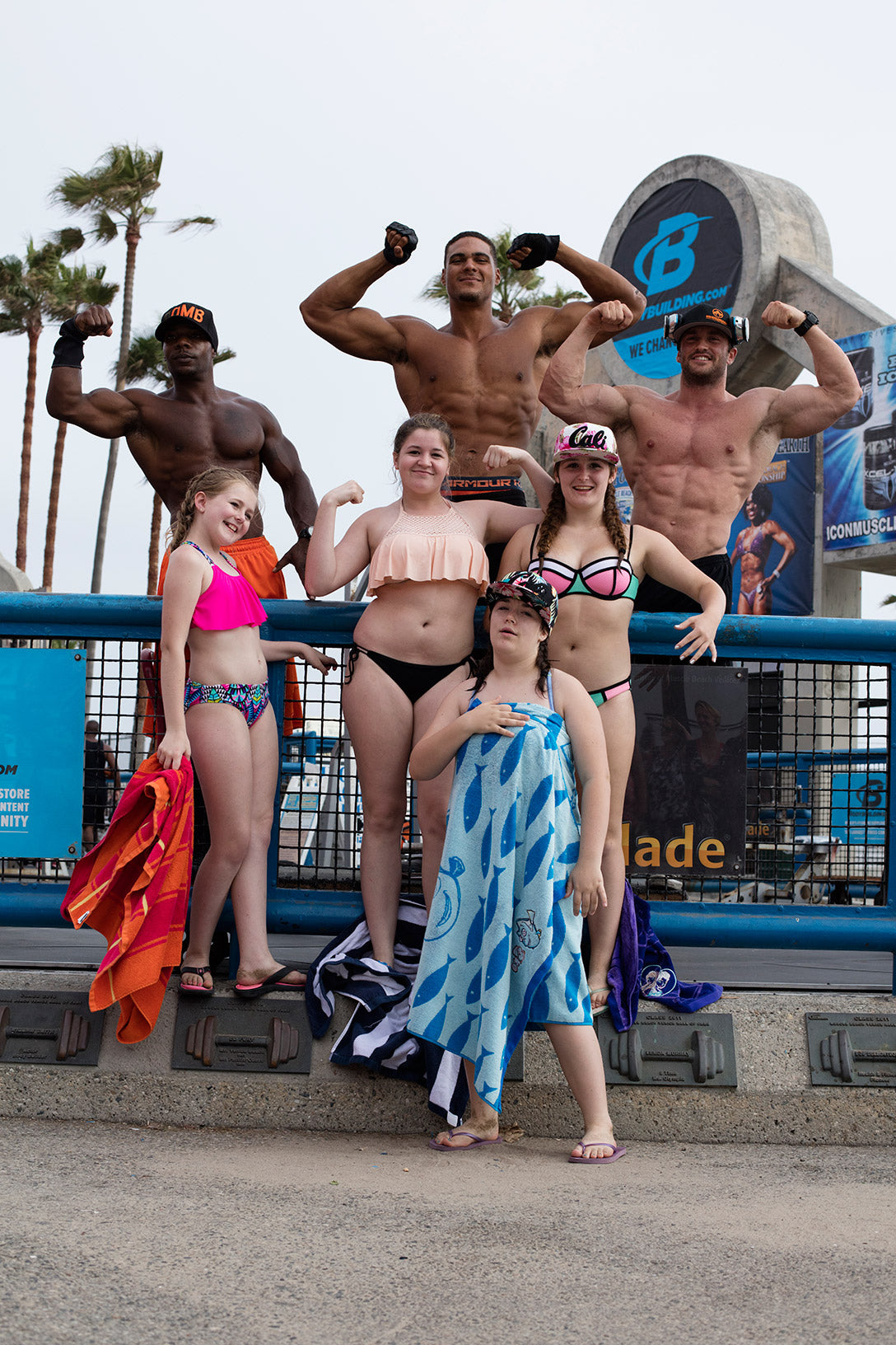 venice beach body builders pose with group of people