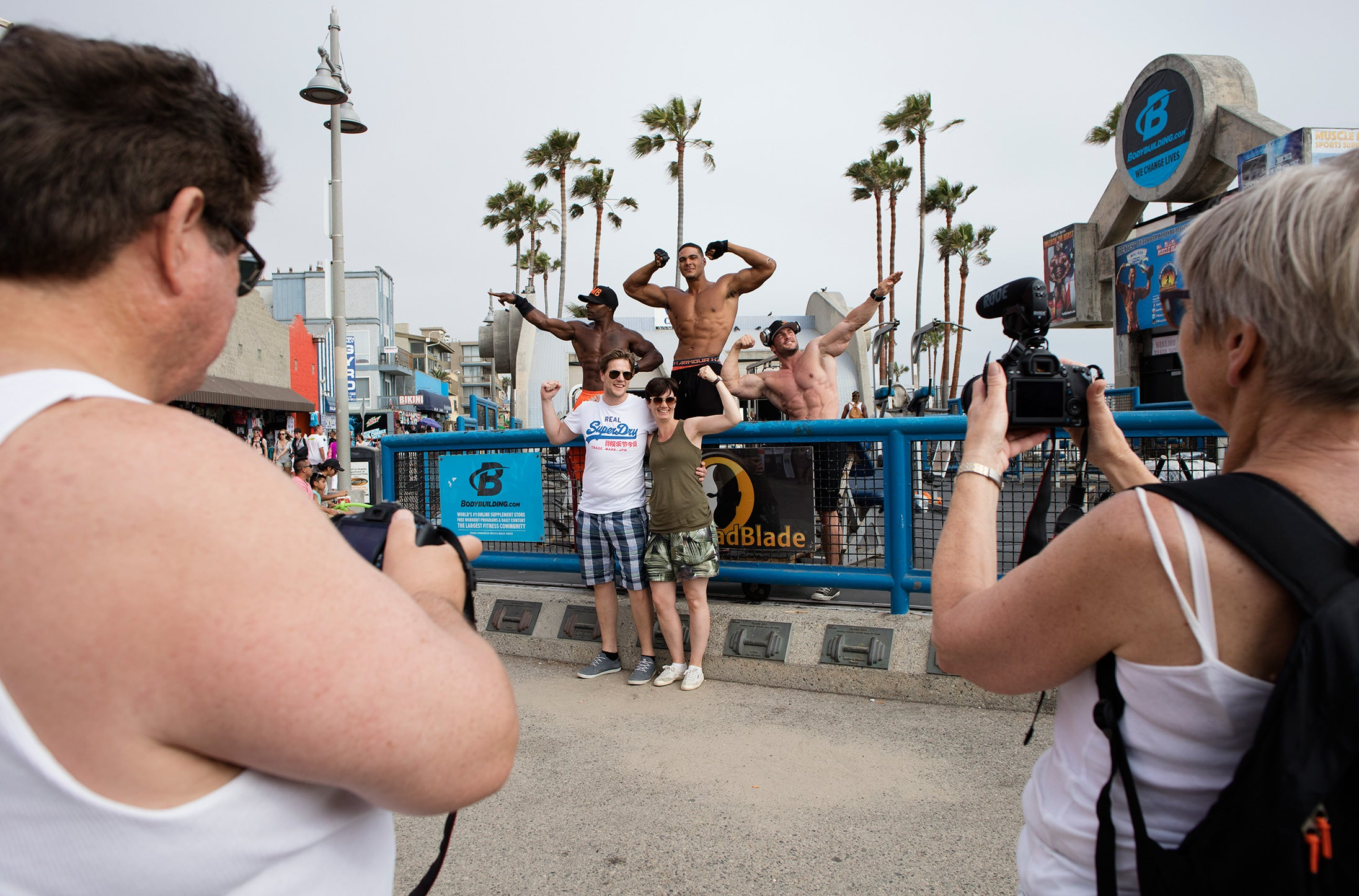 Muscle beach body builders pose with people