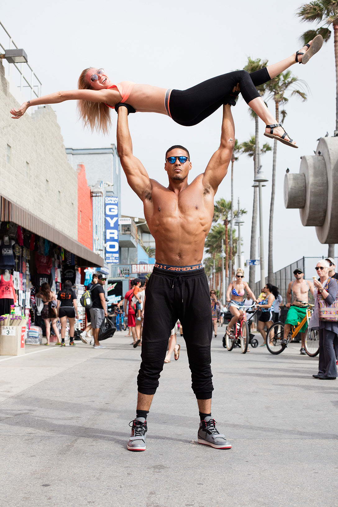Muscle beach body builder poses lifting a person in air