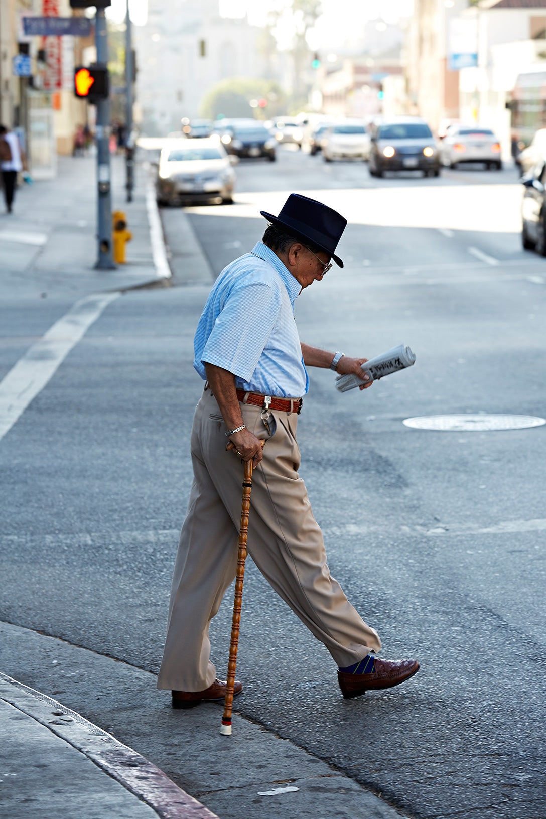 Person walking across street with cane and newspaper