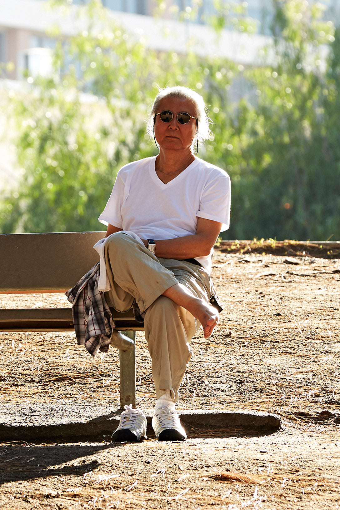 Person sitting on park bench with right shoe off