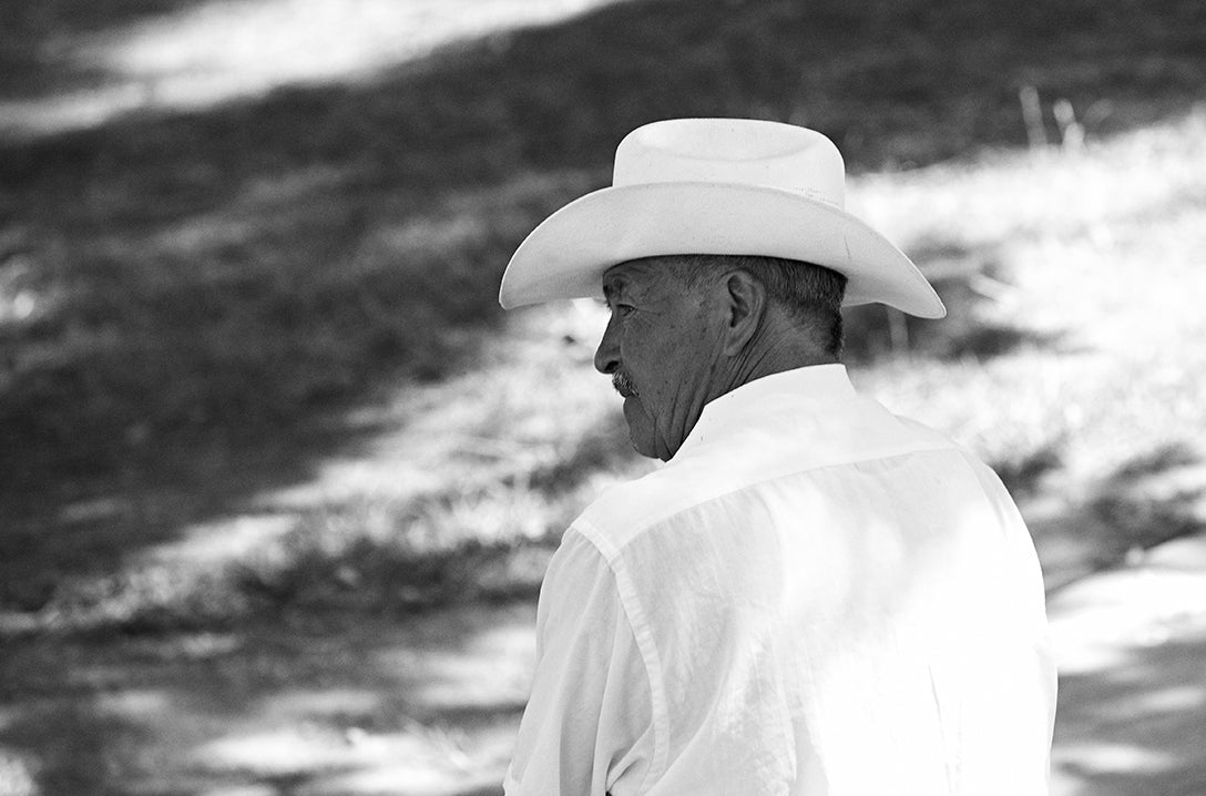 Person in black and white wearing cowboy hat and blouse